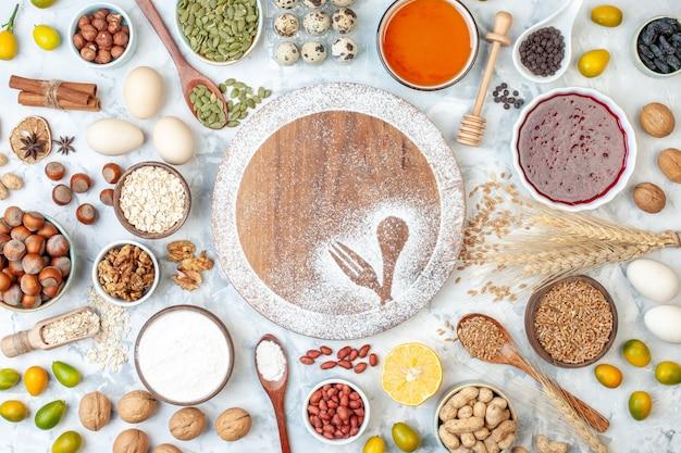 Bovenaanzicht rond bureau met meel eieren gelei en verschillende noten op wit fruit noten suiker kleur taart foto zoet cake deeg