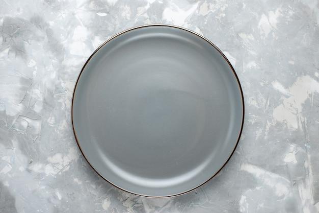 Bovenaanzicht rond leeg bord grijs gekleurd op de lichtgrijze bureauplaat keukenvoedselkleur