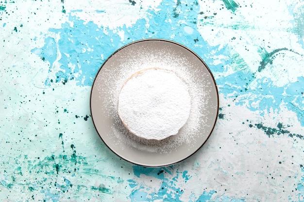 Bovenaanzicht ronde cake met suikerpoeder in plaat op het lichtblauwe oppervlak