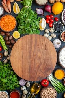 Bovenaanzicht ronde deegplank bonen in kom knoflook citroen tomaat hazelnoot kastanje rode linzen in kom op tafel