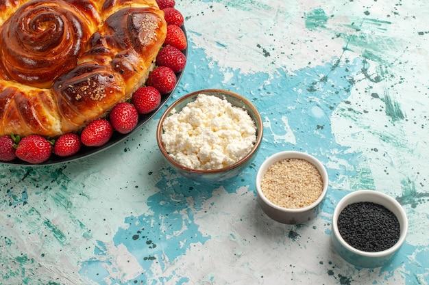 Bovenaanzicht ronde heerlijke taart gebakken en zoete cake met aardbeien op blauwe ondergrond
