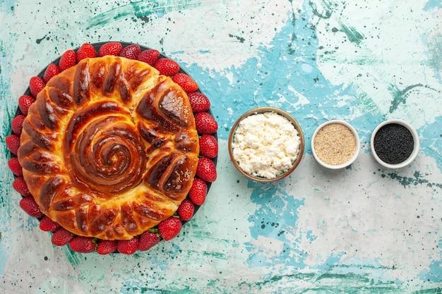Bovenaanzicht ronde heerlijke taart gebakken en zoete cake op blauw bureau
