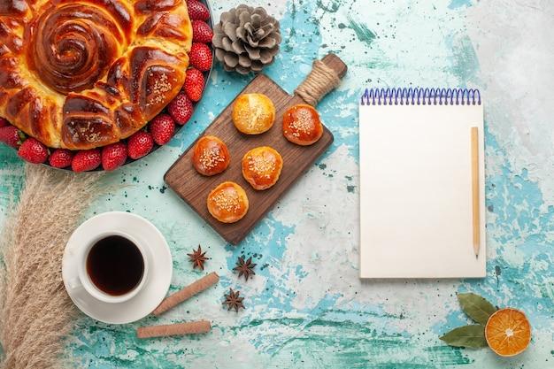 Bovenaanzicht ronde heerlijke taart met kleine cakes van aardbeien en kopje thee op lichtblauw oppervlak