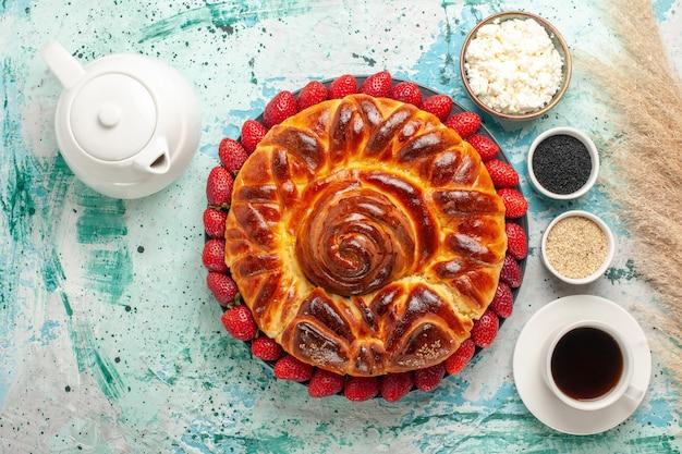 Bovenaanzicht ronde heerlijke taart met verse aardbeien op blauw bureau