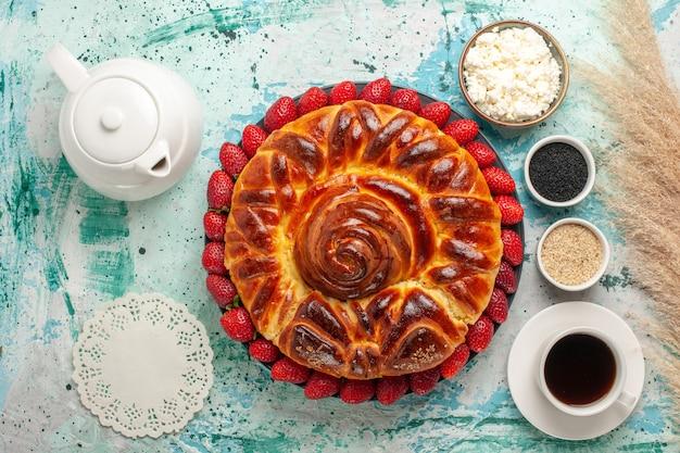 Bovenaanzicht ronde heerlijke taart met verse aardbeien op het blauwe oppervlak