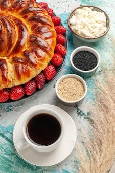 Bovenaanzicht ronde heerlijke taart met verse aardbeien op het lichtblauwe oppervlak