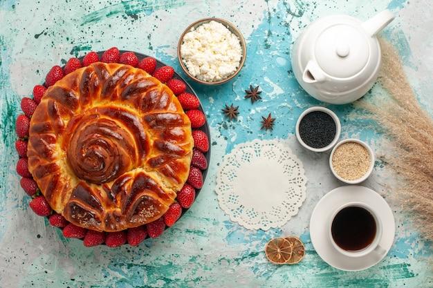 Bovenaanzicht ronde heerlijke taart met verse aardbeien op lichtblauw bureau