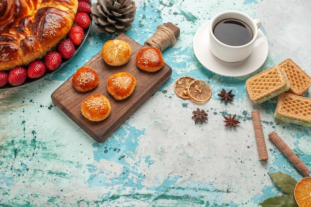 Bovenaanzicht ronde heerlijke taart met verse rode aardbeien en thee op lichtblauw oppervlak