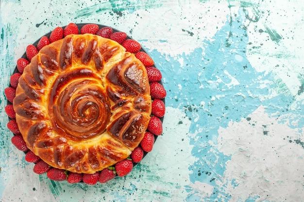 Bovenaanzicht ronde heerlijke taart met verse rode aardbeien op blauw bureau