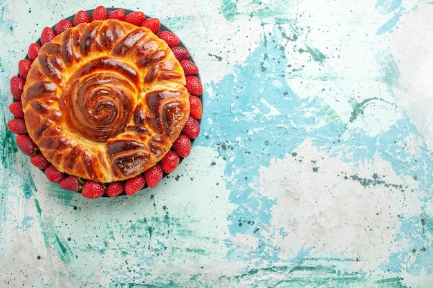 Bovenaanzicht ronde heerlijke taart met verse rode aardbeien op het blauwe oppervlak