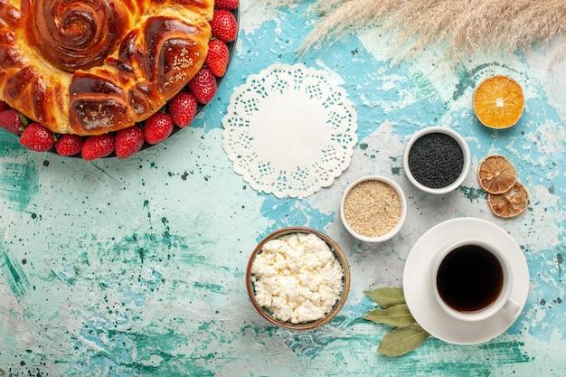 Bovenaanzicht ronde heerlijke taart met verse rode aardbeien op lichtblauw bureau