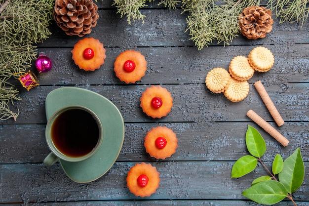 Bovenaanzicht ronde kersen cupcakes fir-tree takken kerst speelgoed kegels verschillende koekjes en een kopje thee op donkere houten tafel