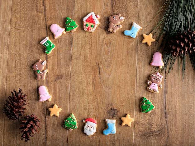 Bovenaanzicht ronde samenstelling van verschillende vorm van zelfgemaakte kerstkoekjes op bruine tafel met dennenblad achter, rustieke sfeer