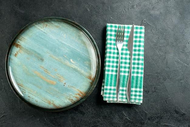 Bovenaanzicht ronde schotel diner mes en vork op groen en wit geruit servet op zwarte tafel vrije ruimte