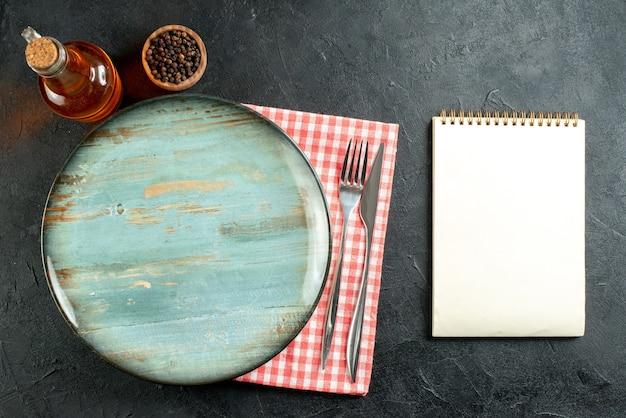 Bovenaanzicht ronde schotel diner mes en vork op rood en wit geruit servet notebook op zwarte tafel