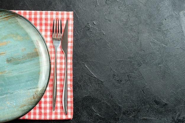 Bovenaanzicht ronde schotel diner mes en vork op rood en wit geruit servet op zwarte tafel met vrije ruimte