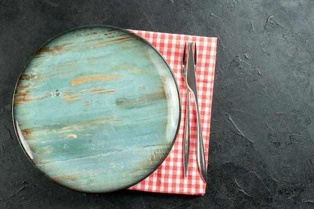 Bovenaanzicht ronde schotel diner mes en vork op rood en wit geruit servet op zwarte tafel vrije ruimte