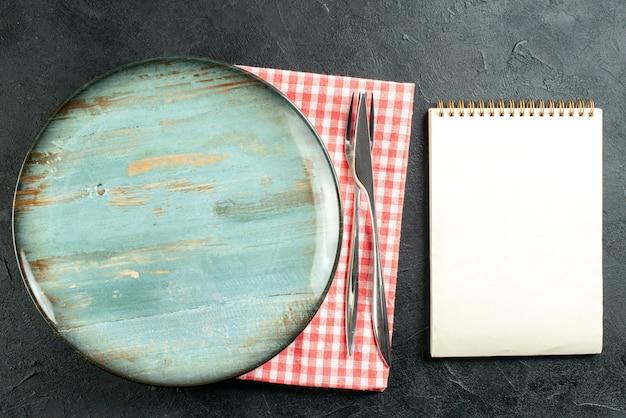 Bovenaanzicht ronde schotel diner mes en vork op rood wit servet kladblok op zwarte tafel