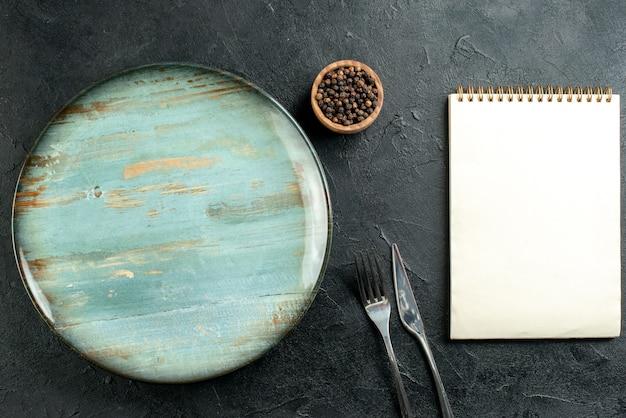 Bovenaanzicht ronde schotel diner mes en vork zwarte peper in kom kladblok op zwarte tafel