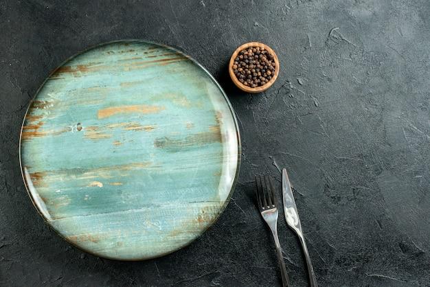 Bovenaanzicht ronde schotel diner mes en vork zwarte peper in kom op zwarte tafel vrije ruimte