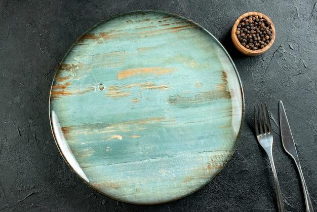 Bovenaanzicht ronde schotel diner mes en vork zwarte peper in kom op zwarte tafel