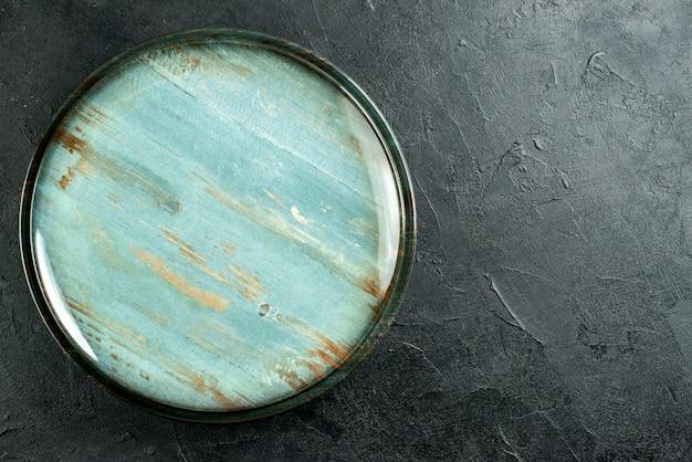 Bovenaanzicht ronde schotel op zwarte tafel met vrije plaats