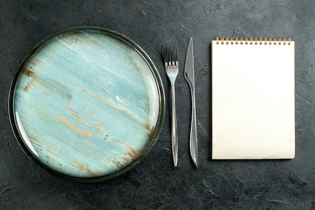 Bovenaanzicht ronde schotel stalen vork en diner mes notebook op zwarte tafel