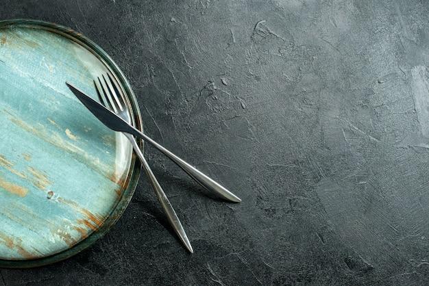 Bovenaanzicht ronde schotel stalen vork en diner mes op zwarte tafel met vrije ruimte