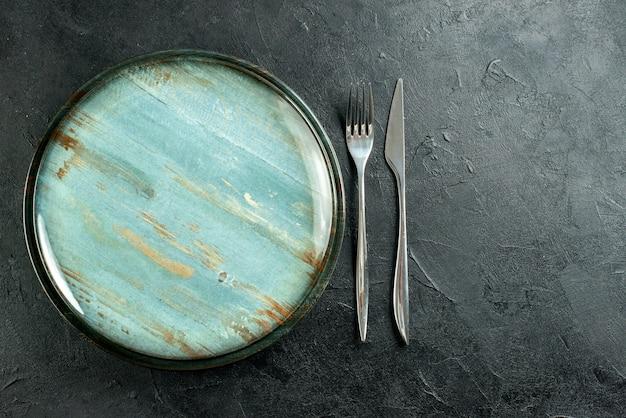 Bovenaanzicht ronde schotel stalen vork en diner mes op zwarte tafel vrije plaats