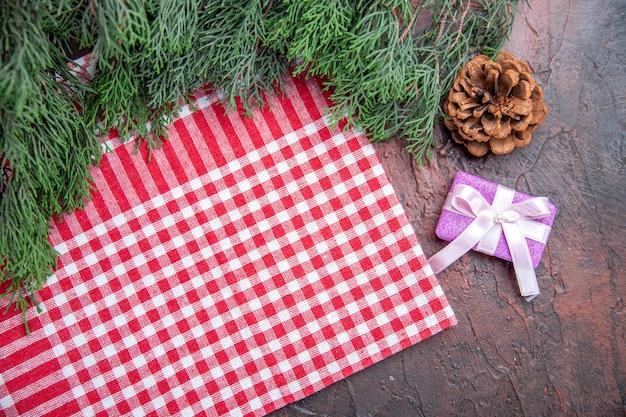 Bovenaanzicht rood en wit geruit tafelkleed dennenboom takken dennenappel kerstcadeau op donkerrode achtergrond