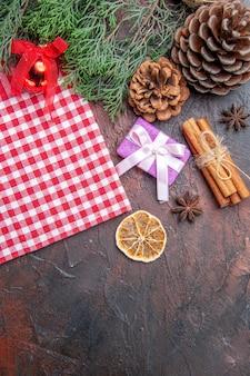 Bovenaanzicht rood en wit geruit tafelkleed pinetree takken dennenappels kerstcadeau kaneel kerstboom bal speelgoed op donkere rode achtergrond vrije ruimte