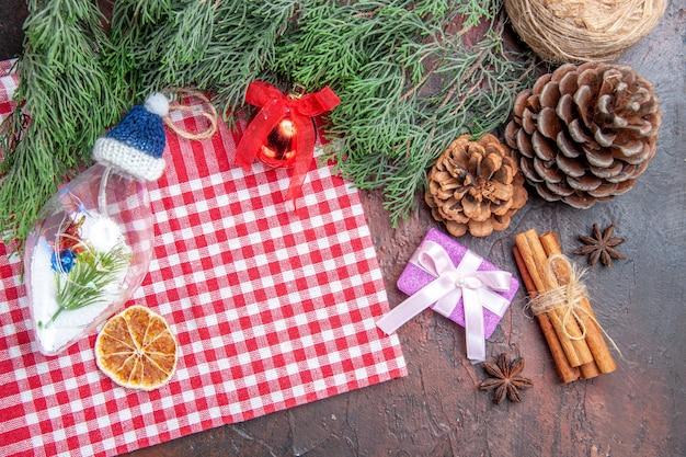 Bovenaanzicht rood en wit geruit tafelkleed pinetree takken dennenappels kerstcadeau kaneel kerstboom speelgoed steranijs op donkerrode achtergrond