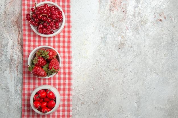 Bovenaanzicht rood fruit met bessen op wit bureau vers fruit bessen