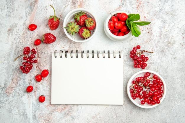 Bovenaanzicht rood fruit met blocnote op wit tafelbes rood fruit