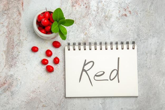 Bovenaanzicht rood fruit met rode geschreven blocnote op wit tafelbes rood fruit