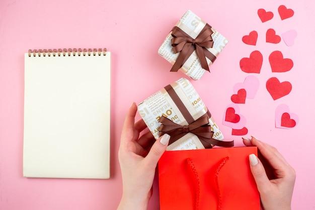 Bovenaanzicht rood hart stickers geschenken in vrouwelijke handen notebook op roze achtergrond