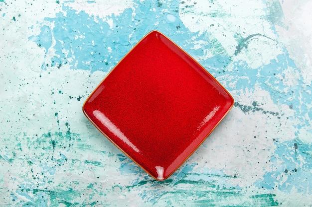 Bovenaanzicht rood plaat vierkant gevormd leeg op lichtblauwe achtergrond