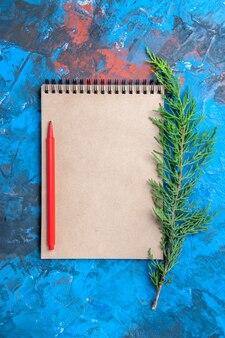 Bovenaanzicht rood potlood op een boomtak van de notebookpijnboom op blauw oppervlak