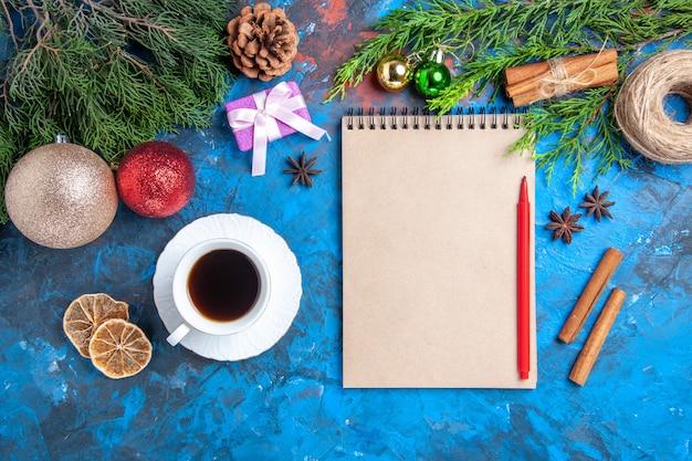 Bovenaanzicht rood potlood op een notebook dennenboom vertakt zich een kopje teaon blauw oppervlak