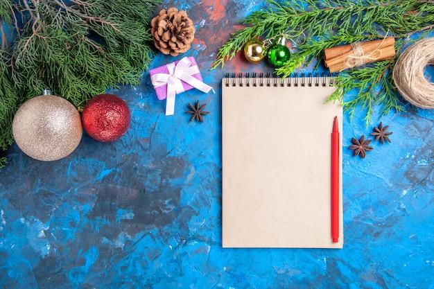 Bovenaanzicht rood potlood op een notebook pijnboomtakken op blauw oppervlak met vrije ruimte