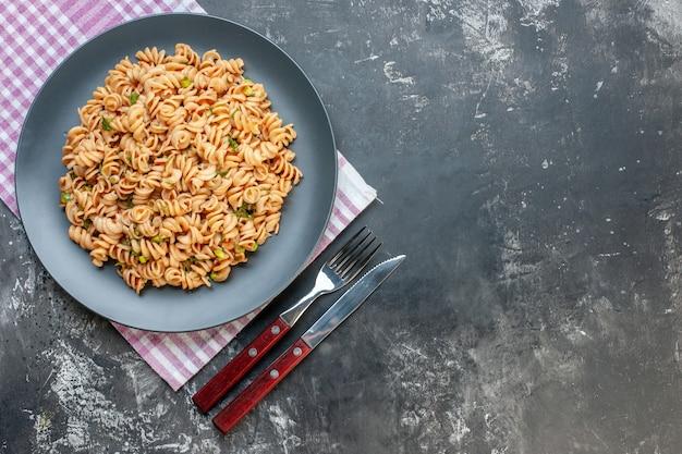Bovenaanzicht rotini pasta op grijze plaat op roze wit geruite servet vork en mes op grijze tafel met vrije ruimte
