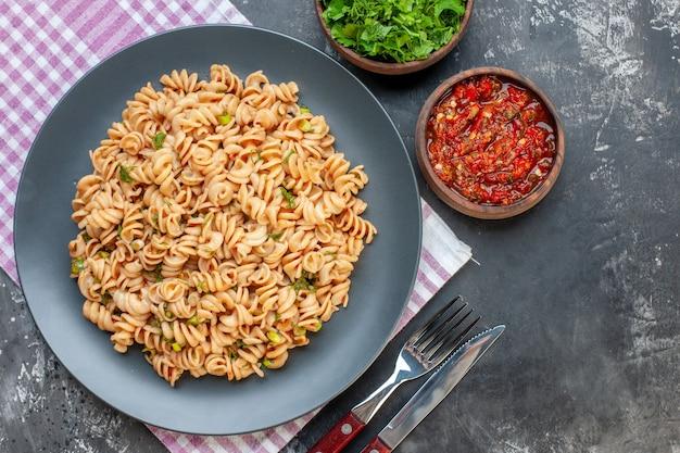 Bovenaanzicht rotini pasta op plaat op roze wit geruite servet vork en mes gehakte greens en tomatensaus in kommen op grijze tafel
