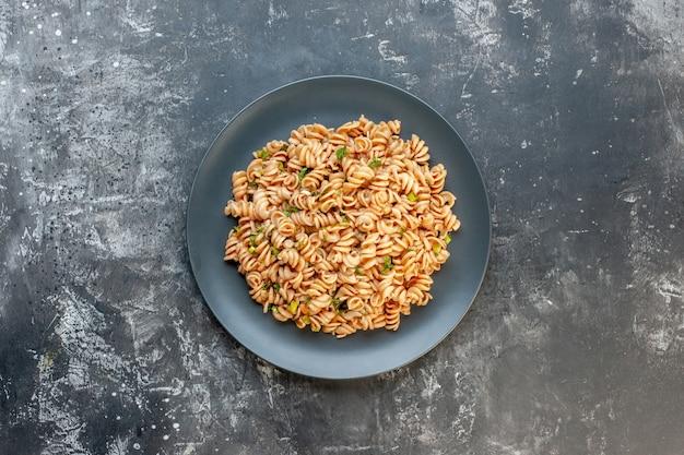 Bovenaanzicht rotini pasta op ronde plaat op donkere ondergrond met kopie plaats