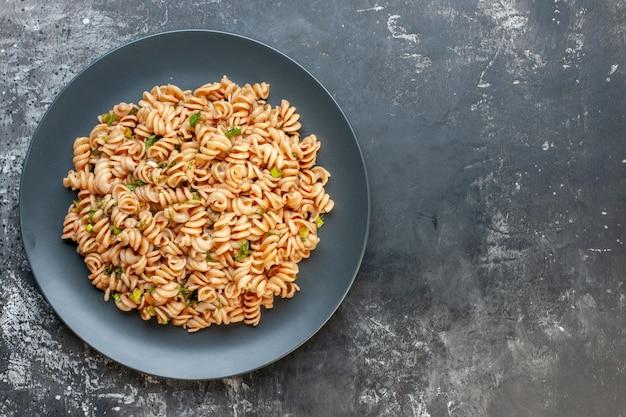 Bovenaanzicht rotini pasta op ronde plaat op donkere ondergrond met vrije ruimte