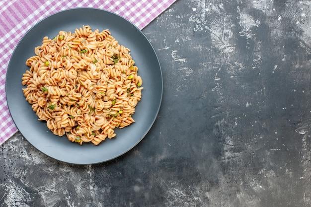 Bovenaanzicht rotini pasta op ronde plaat op roze wit geruit tafelkleed op donkere ondergrond met kopie ruimte