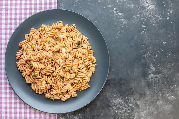 Bovenaanzicht rotini pasta op ronde plaat op roze wit geruit tafelkleed op donkere ondergrond met vrije ruimte