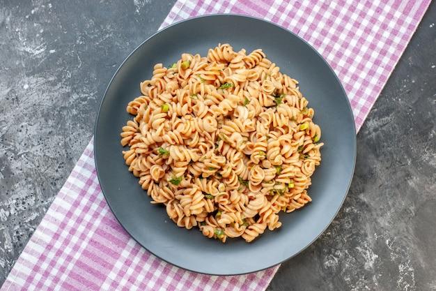 Bovenaanzicht rotini pasta op ronde plaat op roze wit geruit tafelkleed op donkere ondergrond