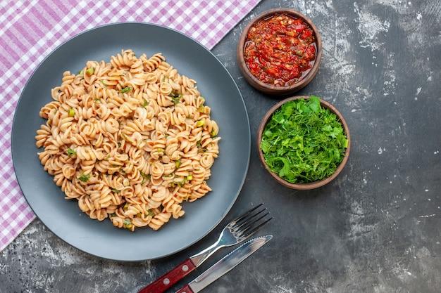 Bovenaanzicht rotini pasta op ronde plaat op roze wit geruit tafelkleed tomatensaus en gehakte greens in kleine kommen mes en vork op donkere ondergrond