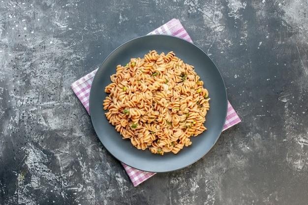 Bovenaanzicht rotini pasta op ronde plaat op roze witte geruite keukenhanddoek op donkere oppervlak kopie plaats