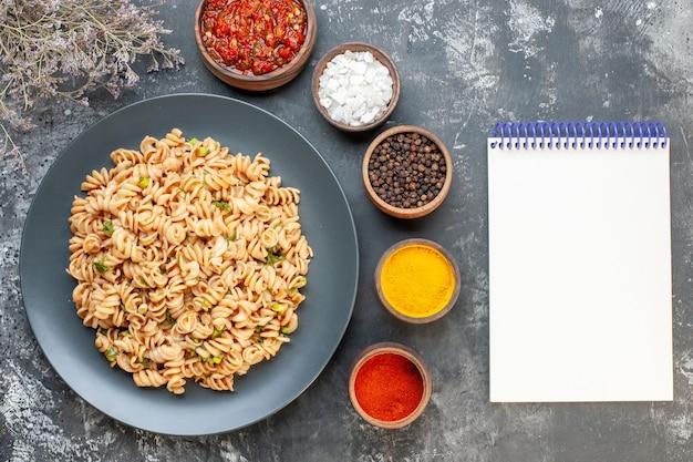 Bovenaanzicht rotini pasta op ronde plaat tomatensaus verschillende kruiden in kleine kommen notebook op donkere tafel